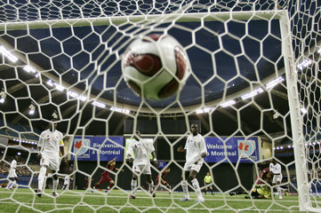 Players from Gambia look on as a Portugal goal enters the net during play at the FIFA Under-20 World Cup soccer tournament in Montreal