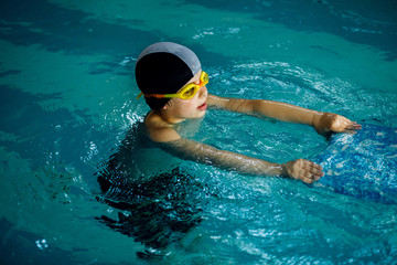 The boy who learns to swim with board in the pool