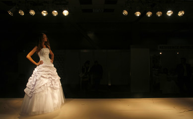 A model presents a bridal outfit during a wedding fair in Bucharest