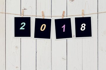 Four photo frame and text 2018 for New Year hanging on white wood background with space.