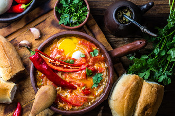 "Traditional chilean dish ""spicy hot"" -- ""picante caliente"" eggs with chili, tomatoes and onion"
