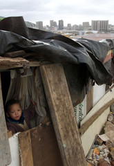 A CHILD STARES OUT OF A CAPE TOWN SHACK.