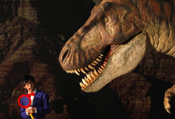 """A host talks in front of a Tyrannosaurus rex replica display named Kokoro during a media preview of the """"Playing with Dinosaurs"""" exhibition at the National Chiang Kai-Shek Memorial Hall in Taipei, Taiwan"""