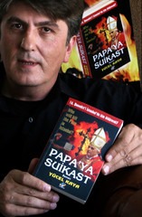 Novelist Kaya poses with his book in his office in Istanbul
