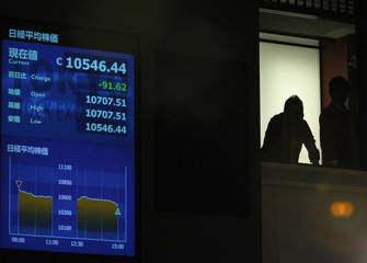 A man is silhouetted next to a stock index board during a ceremony marking the end of trading for 2009 at the headquarters of Tokyo Stock Exchange in Tokyo