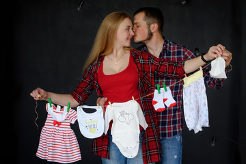 Happy couple man kissing his pregnant woman and they together hung to dry washed newborn baby clothes