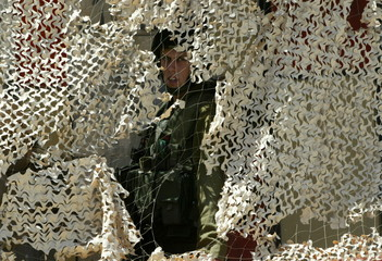 An Israeli soldier peers through a camouflage net at the entrance of the Old City in the West Bank t..