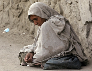 Afghan woman waits for alms in Kabul.