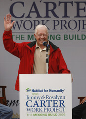 Former U.S. President Carter waves hands while talking with volunteers in Dong Xa village, east of Hanoi