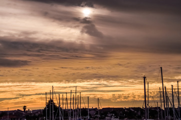 Silhouettes of boats on marina during cloudy yellow sunset in Oxnard, California