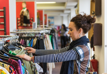Woman browsing through Thrift Store clothing