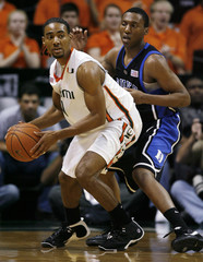 Miami's Hurdle looks to pass off against the defense of Duke's Smith during the first half of their NCAA basketball game in Coral Gables