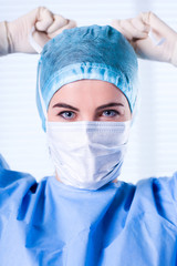 Female Surgeon wearing protective uniforms, cap and mask