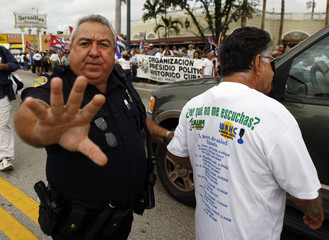 A Miami police officer takes away a Cuban American during a protest of Codepink, a peace organization against anti-communist Cuban activist Posada Carriles in Miami's Little Havana