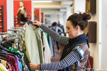 Woman browsing through vintage Thrift Store  clothing