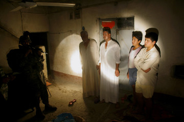An Iraqi family stands as U.S. soldiers search their house for weapons in the town of Al-Meshahda