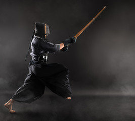 Man is practicing kendo martial arts in traditional armor .He attack with  bamboo sword shinai.