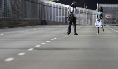 A woman poses for a picture along part of the floodlit formula one night circuit in Singapore