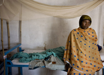 A woman sits on her friend's bed at a health clinic in eastern Chad