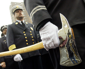 A firefighter carries an axe during the FDNY Memorial Day event in New York, October 12, 2002. Firef..