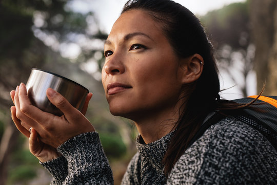 Female hiker resting outdoors with a coffee