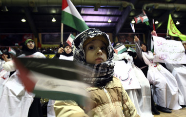 An Iranian child waves a Palestinian flag at an anti-Israel rally in Tehran