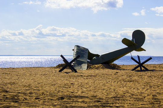 Shot down a plane from the times of World War II on the beach in the sand near the sea