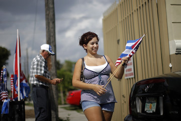A woman buys a Cuban and a U.S. flag in the Little Havana neighborhood of Miami