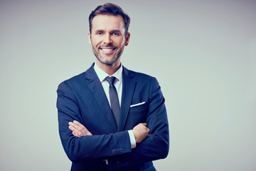 Portrait of handsome man standing with crossed arms, wearing suit smiling. Isolated