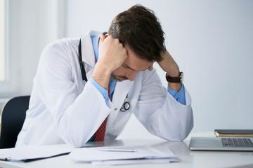 Overworked doctor doing paperwork