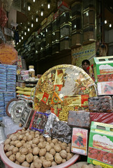 Kashmiri shopkeeper sits behind decorated packs of dried fruits during Ramadan at a market in Srinagar