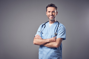 Happy doctor in blue uniform smiling isolated