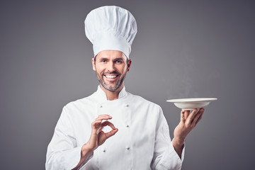 Happy chef holding steaming plate