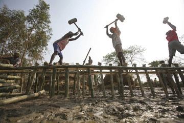 Villagers rebuild an embankment after it got washed away by tidal wave in Sundarbans