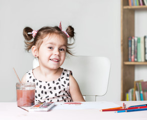 Pretty and cute little girl painting picture with watercolor in studio. Concept of education process.