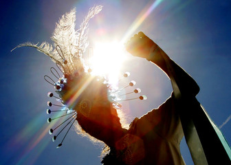 A carnival-goer in costume is silhouetted against the sun as he dances at the annual Notting Hill ...