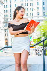 American female college student reading book, studying on campus in New York in summer