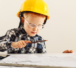 Young boy want to be engineer.He examining blueprint.