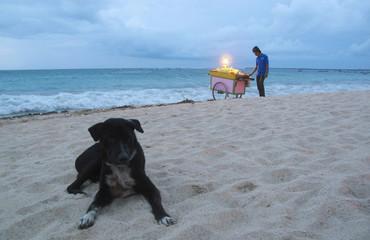 A man sells grilled corn on a beach in Jimbaran