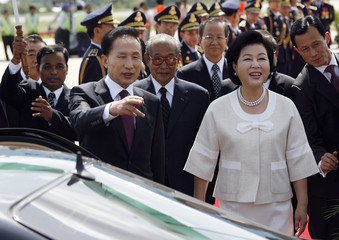 South Korea's President Lee walks with wife Kim upon their arrival at Phnom Penh international airport