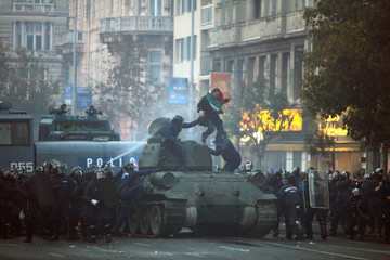 Police pull a demonstrator out of a tank which was being driven towards riot police during an anti-government protest in Budapest
