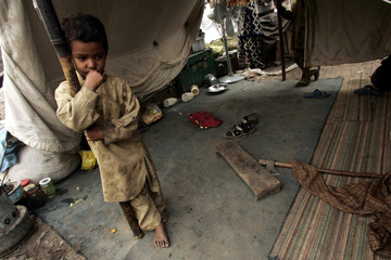 Kashmiri earthquake survivor stands next to makeshift shelter in Muzaffarabad