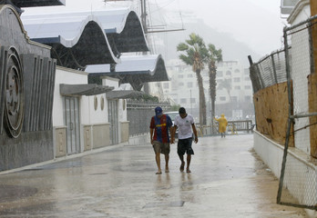 People walk on a street in Cabo San Lucas
