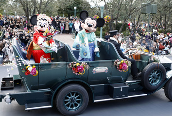 Disney cartoon characters Mickey and Minnie Mouse, dressed in kimonos, wave from an open car during a New Years parade at Tokyo Disneyland in Urayasu