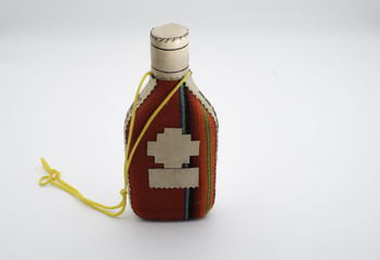 Small bottle wrapped in colorful wool textile