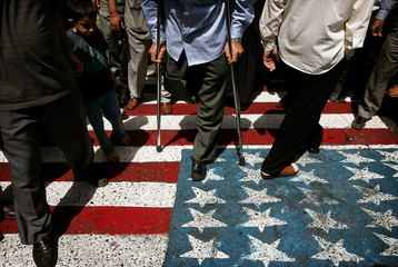 Iranian voters walk on a US flag painted on the pavement as they enter a polling centre in Tehran.