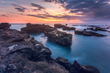 breathtaking cloudy sunset during low tide at mengening beach, Bali
