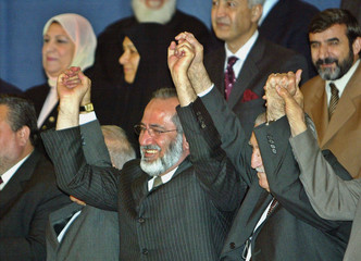MEMBERS OF THE IRAQI GOVERNING COUNCIL CELEBRATE AFTER THE SIGNING CEREMONY IN BAGHDAD.