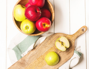 Red and green apples on a white wooden background, horizontal, soft focus, top view