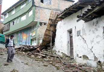 A man walks past a damaged house in Quetame